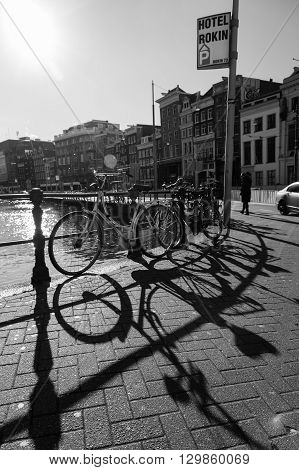 AMSTERDAM NETHERLANDS - 16TH FEBRUARY 2016: Bikes attached to railings along the Amsterdam canals. Shadows can be seen from the bikes. People can be seen in the distance.