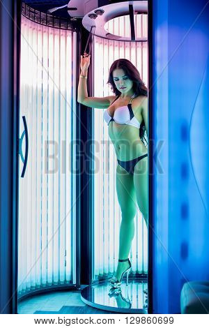 Image of beautiful woman sunbathing in solarium