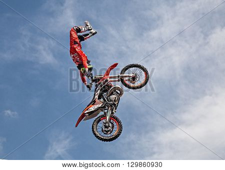 VOLTANA DI LUGO (RA) ITALY - APRIL 10: freestyle motocross show in the public town square; a stunt biker make a jump and performing an acrobatic figure in flight during the motorcycle rally