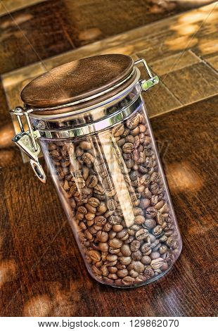 Coffee beans in glass container on wooden table.Taken closeup.
