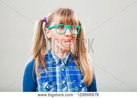 Studio shot portrait of nerdy woman who is making funny face