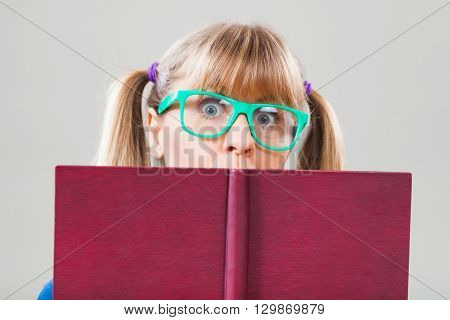 Studio shot portrait of nerdy woman who is holding book
