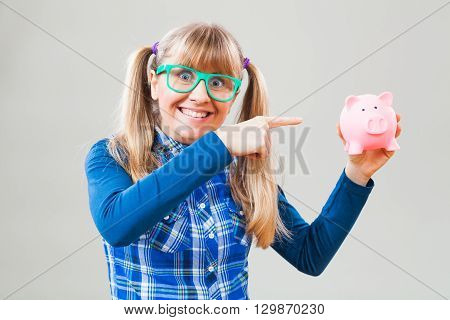Studio shot portrait of happy nerdy woman who is pointing at piggy bank