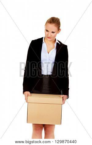Sad business woman carrying box after loosing job