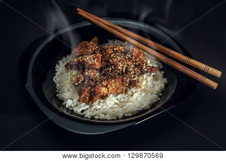 Chicken teriyaki with steamed rice on black background.
