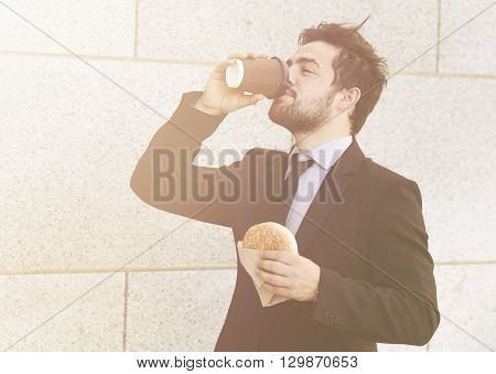 Tonedpicture of handsome businessman eating junk food and drinking tea or coffee on to go to work. Freelancer man in hurry having snack.