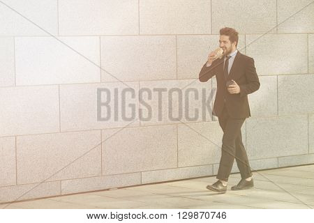 Toned picture of businessman in full length walking to office and eating junk food and drinking cup of tea or coffee along street.