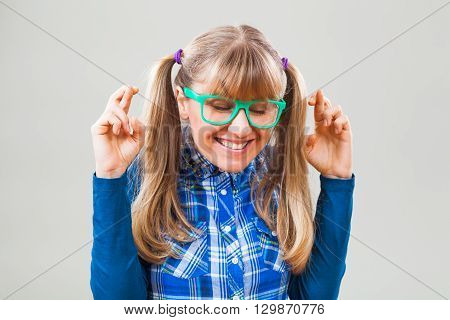 Studio shot portrait of cheerful nerdy woman with fingers crossed
