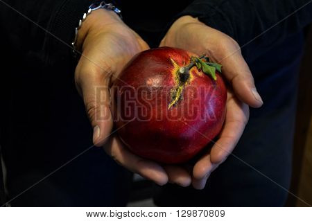 Male hands cupping a vivid red pomegranate creates a heart shape