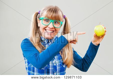 Studio shot portrait of happy nerdy woman who is pointing at apple