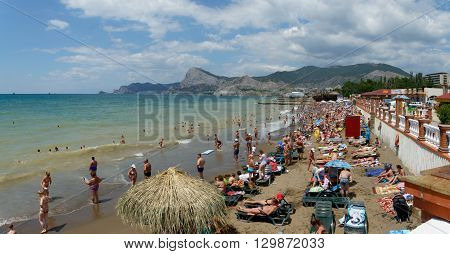 SUDAK, RUSSIA - JUNE 27: Holidayers are visiting beach of Sudak resort on June 27, 2015 in Crimea, Russia.