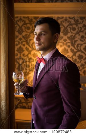 groom drinking wine is going to the wedding looking away