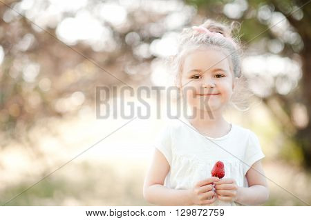 Cute kid girl 3-4 year old eating strawberry outdoors. Looking at camera. Childhood. Happiness.