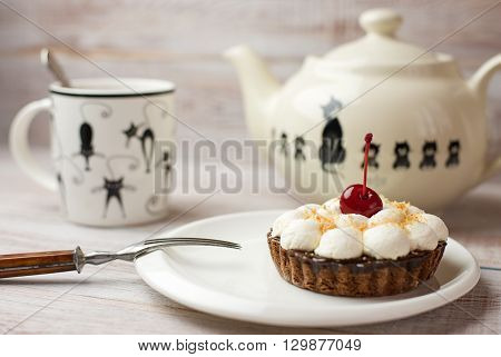 Cup tea and cake with a cherry on the table