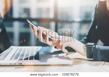 Photo Woman Working Modern Smartphone and Wearing Generic Design Smart Watch.Female Hands Touching screen phone.Manager Work Process.Laptop on the wood Table.Horizontal, Burred background.Film effects.