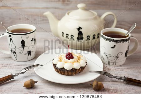 Two Cups of tea and cake with a cherry on the table