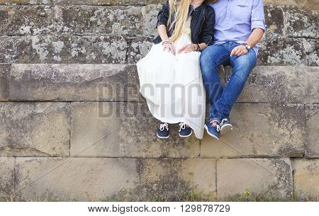Close up hands of a young couple holding hands outdoors