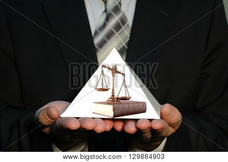 Businessman holding blank pyramid whit scales of justice on the book