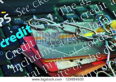 Credit cards with chain on the keyboard of computer and dictionary definition of credit SOFT FOCUS