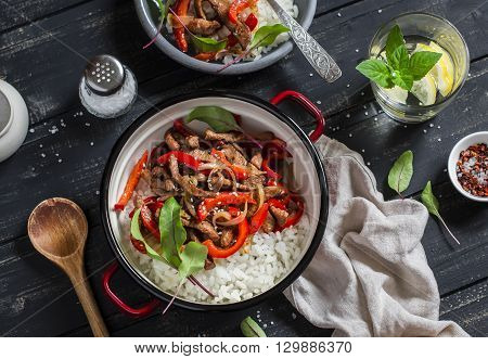 Meat stir fry with red peppers and rice in a pot homemade lemonade with lemon on a dark wooden background. Delicious healthy lunch. Top view