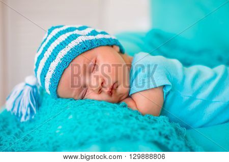 The baby sleeps on the tummy in a striped cap with a pompon