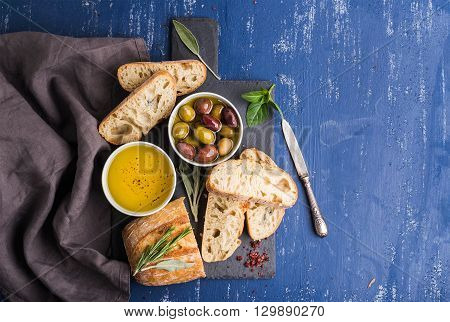 Mediterranean snacks set. Olives, oil, herbs and sliced ciabatta bread on black slate stone board over painted dark blue background, top view, copy space