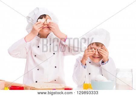 two little cooks in white uniform holding pieces of dough like eyes