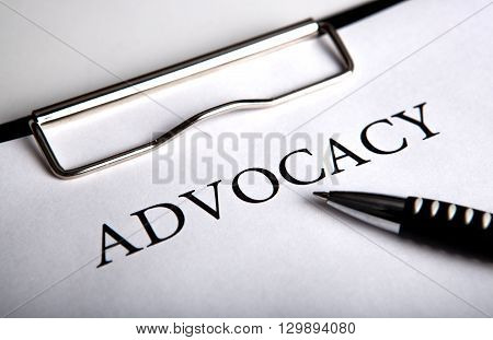document with the title of advocacy and pen close up