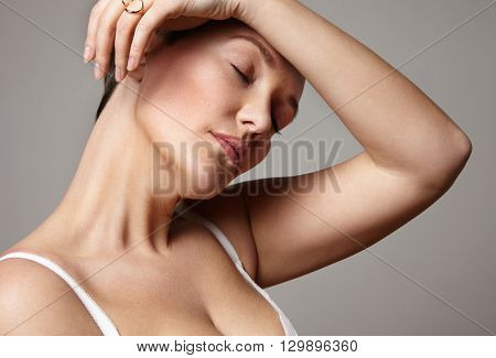 woman with a headache touching forehead with closed eyes
