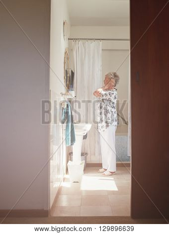 Full length indoor shot of elderly woman getting ready at dresser. Senior female getting ready in bathroom. poster