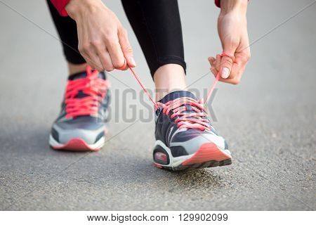 Woman Lacing Running Shoes. Close-up