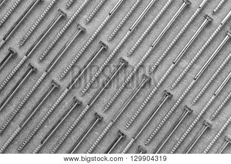 set of new metal screws on a grey background are on the diagonal. black and white photo. Flat lay top view