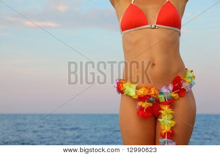 beautiful young woman dressed in bathing suit stands on beach. Hawaiian garland of flowers at the waist