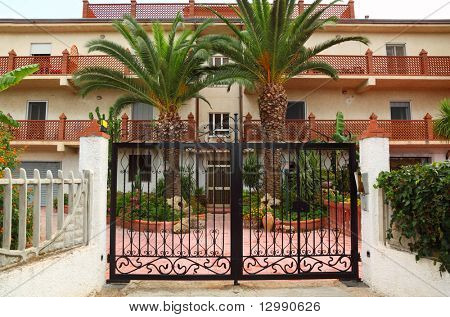 Forged black gate of sanatorium. palm trees and buildings of sanatorium can be seen outside gates