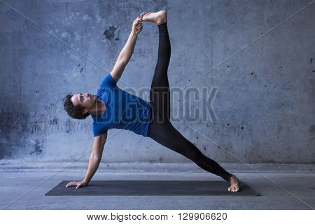 Young man practicing yoga. Side plank pose, vasisthasana in Sanskrit.