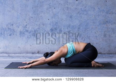 Young woman practicing yoga, childs pose, resting.