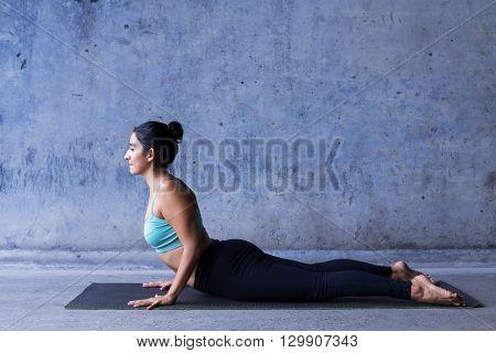 Young woman practicing yoga. Cobra, or bhujangasana