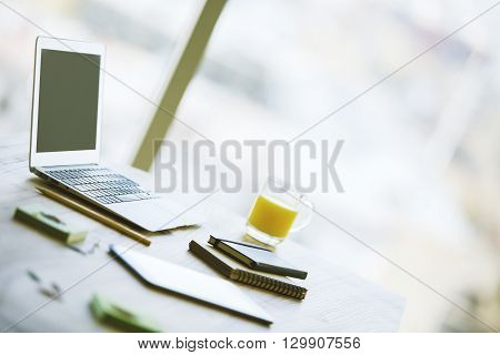 Sideview of office desk with blank laptop screen orange juice smartphone notepads and other items on blurry background