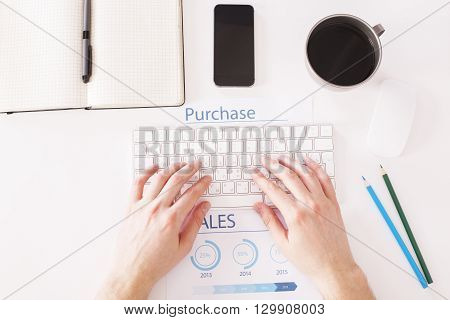 Topview of white desktop with businessperson hands typing on keyboard placed on business report