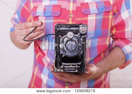 Front view of man's body with retro camera in hands