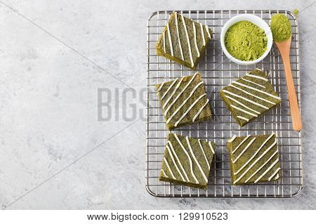 Matcha green tea brownie cake with white chocolate on a cooling rack Grey stone background. Top view Copy space