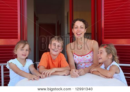 Woman with three children sits in  number on  verandah   table with  white table-cloth and laughs