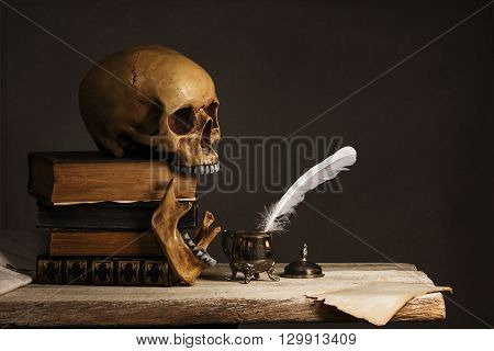 Skull on old Book with empty Page Feather and Inkpot