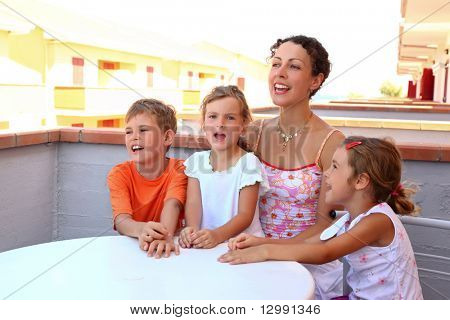Mother and three children sit on  verandah in summer near  table and yell merrily