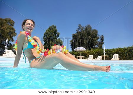 In  pool in  day-time  woman sits in  blue swimming suit and necklace from colors, underwater package