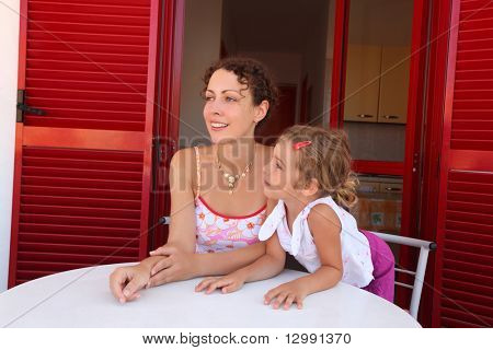 Daughter and mother sit on  verandah  round table near  door and look aside