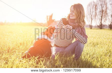 Smiling lady taking free time with her dog.Woman relaxing in the nature with her loyal dog