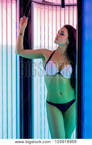 Bodycare. Image of attractive woman tans in solarium