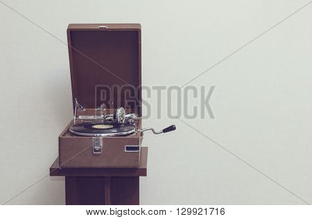 Old retro portable gramophone isolated vintage style toned with empty space poster