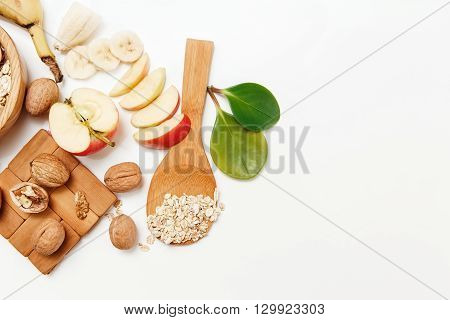 There are BananaApleOrange with Walnuts in the Wooden Plate and Rolled Oats,Wooden Spoon,Green Leaves,Healthy Fresh Organic Food on the White Background,Top View